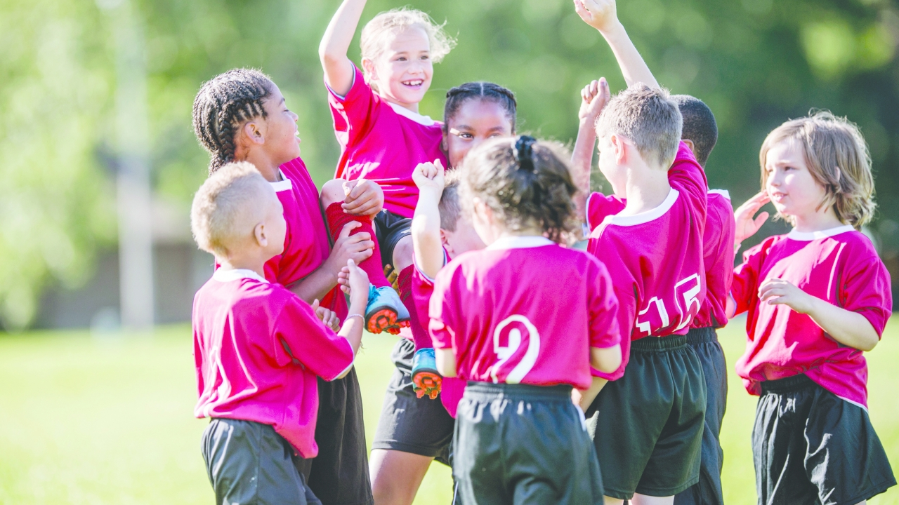 A multi-ethnic group of elementary age children are standing together in a row after their soccer game. They are cheering and holding up their teammate.